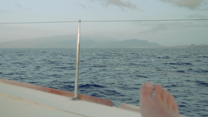 View of Madeira island and man's toes in morning. View from board of sailing yacht | Shutterstock HD Video #1011234509