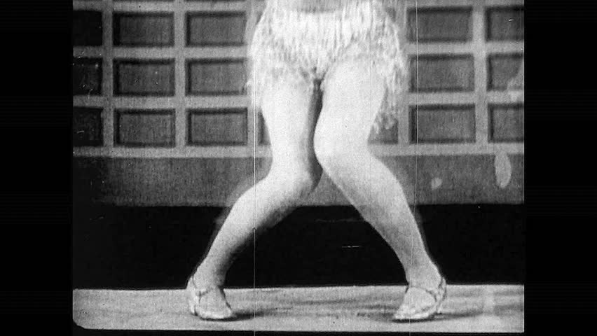 1920s: Woman's legs as she dances. Two women dancing together. Group of women dancing in circle in public. Large crowd watches women dance.