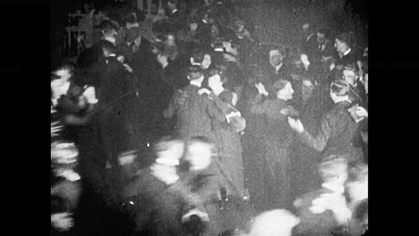 1920s: People dancing in club. Band plays on floor while people dance around them. Couple dancing. Different couple dancing. Two girls dance.
