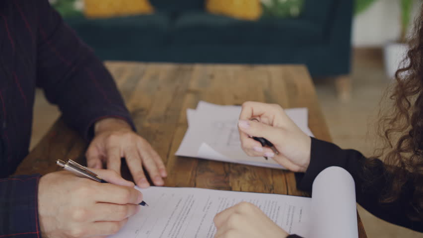 Close-up shot of male hand signing purchase and sell agreement and taking house keys from realtor then shaking hands. Selling and buying real estate concept. #1011250166