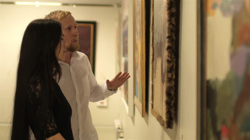 couple discuss paintings in the museum's art gallery
