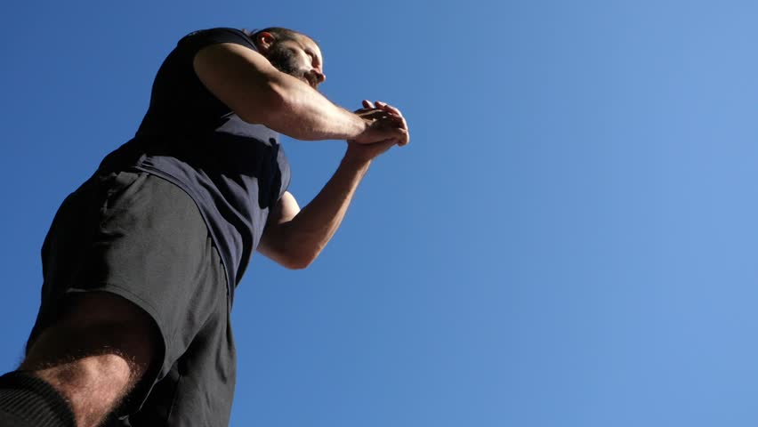 Bearded man in a black T-shirt  makes squats. Outdoor fitness training.  #1011270785