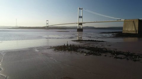 Drone tracks low and sideways over river bank with Severn Bridge behind. Taken on a beautiful spring evening
