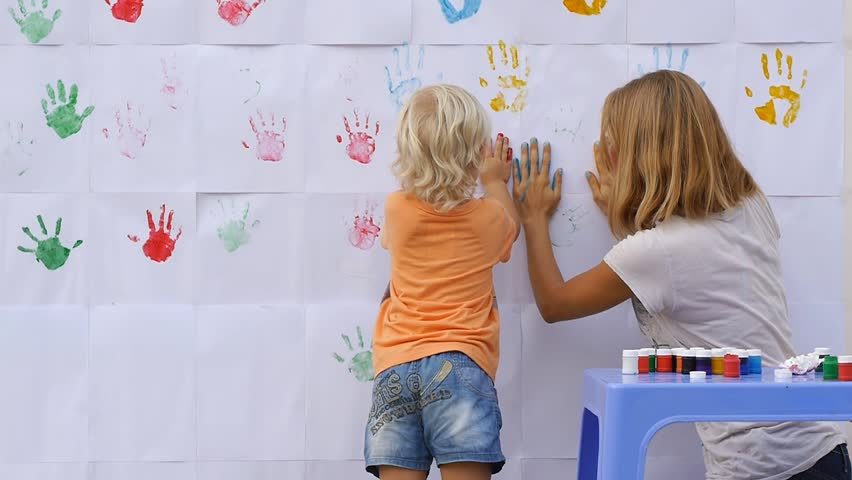 A little cute happy funny child painting color handprints on the white wall with smiling mother together and giving five by hands in print 50fps #10112807