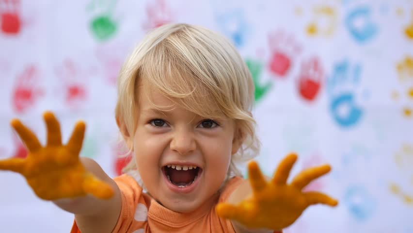 A little cute happy child scaring by hands in colorful print and smiling on color handprints background in slow motion 50fps #10112816