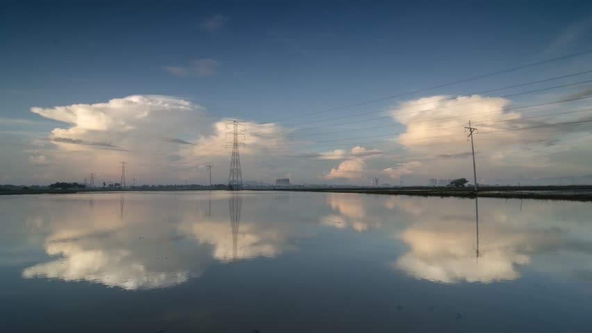 Timelapse white cloud over electric tower under blue sky.