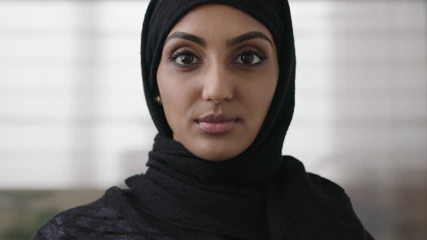 close up portrait of independent young muslim business woman looking serious confident at camera wearing traditional headscarf slow motion #1011299813