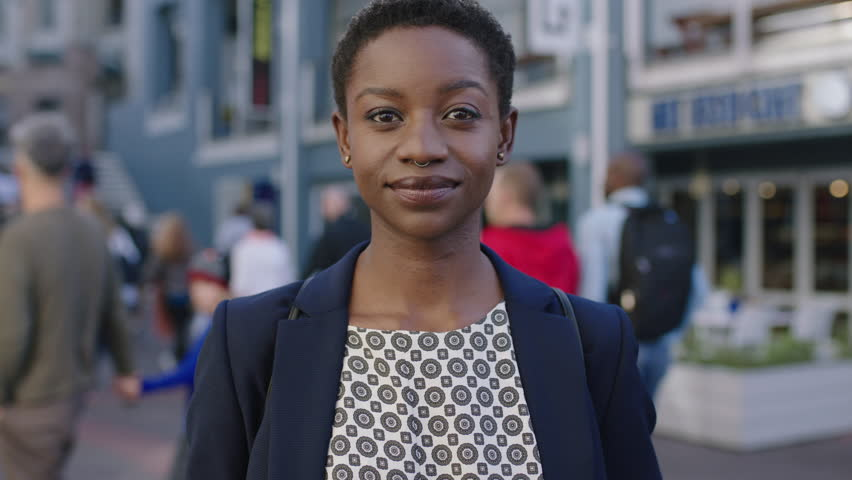 portrait of independent african american business woman looking serious confident at camera in urban background wearing nose ring #1011299873