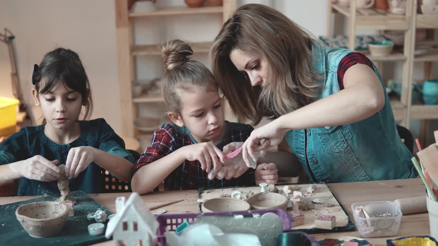 Mother and daughter enthusiastically molded from clay in the pottery. | Shutterstock HD Video #1011315710