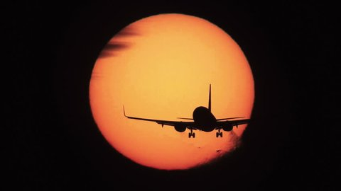 Silhouette of jumbo jet landing with big sun in the background, high contrast super slow motion