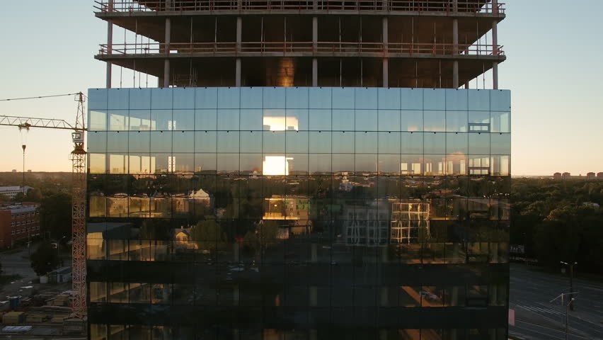 Aerial Shot of the Skyscraper Building in the Process of Construction. In the Background Working Crane, Forest, sea and Sunset. Shot on 4K UHD Camera.