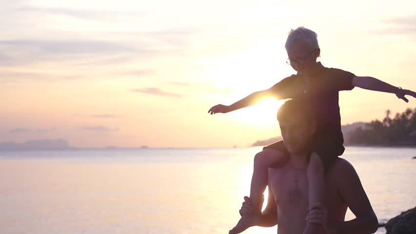 A joyful son sits on his father's shoulders, arms outstretched against the backdrop of a beautiful sunset on the sea. slow motion, 1920x1080, full hd #1011330401