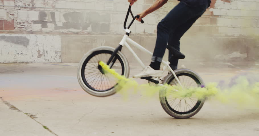 Extreme BMX biker doing tail whip with purple and yellow colored smoke grenade trick in urban environment | Shutterstock HD Video #1011342083
