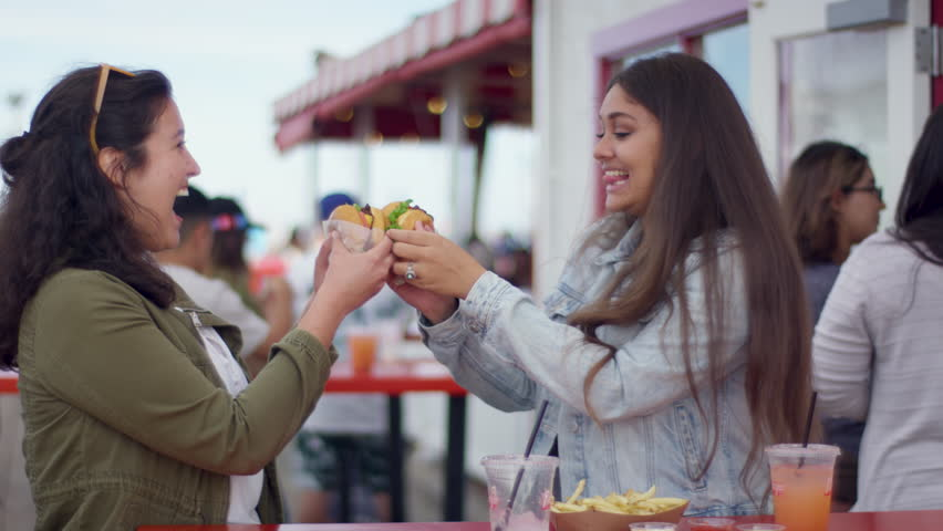 Best Friends Cheers With Their Burgers, Then Really Enjoy Taking First Bite, On Santa Monic Pier (Shot On Red Scarlet-W Dragon In 4K, Slow Motion)
