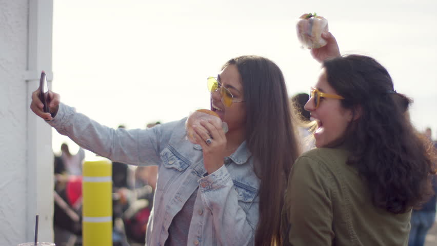 Excited Young Women Pose With Their Burgers For Fun Vacation Selfies On The Santa Monica Pier (Shot On Red Scarlet-W Dragon In 4K, Slow Motion) Royalty-Free Stock Footage #1011346895