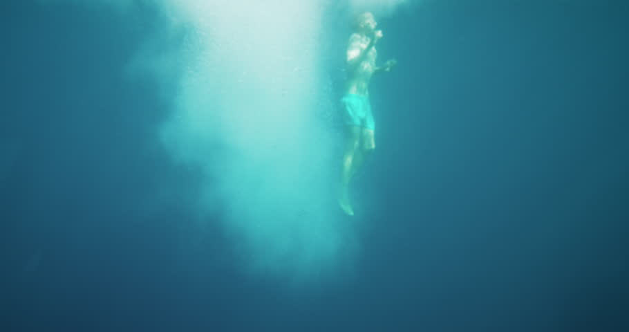 Underwater Footage of Man Jumping into Water and Swimming. Diving in the Ocean. Shot on RED Epic 4K UHD Camera.