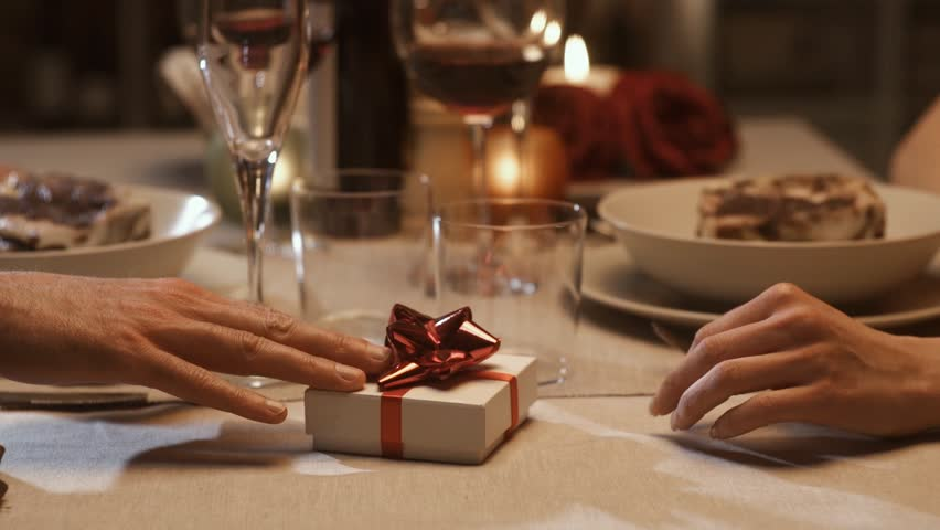 Couple having a romantic dinner date at the restaurant and celebration St Valentine's day, the man is giving a precious gift to his girlfriend, feelings and relationships concept
