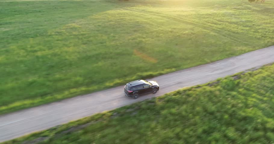 Aerial view of crossover SUV car driving along the empty gravel road through green meadows landscape on sunny morning. Drone chasing a car.