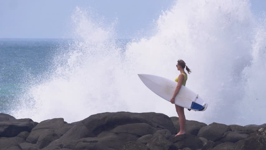 SLOW MOTION, COPY SPACE: Spectacular shot of water splashing while surfer girl stands still on a beautiful black beach. Powerful ocean waves hit the rocky shore. Female tourist looking into distance.