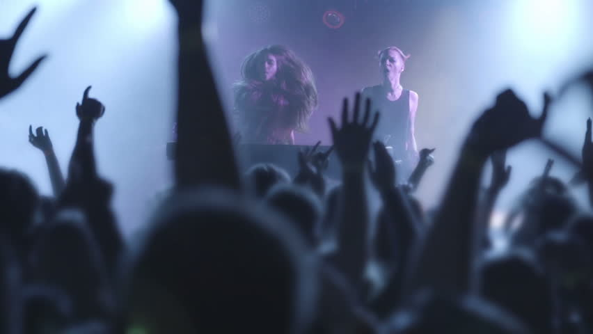 Two beautiful young women DJ play the music on the mixing console in the nightclub. Against the background of unrecognizable people. Slow motion | Shutterstock HD Video #1011370964