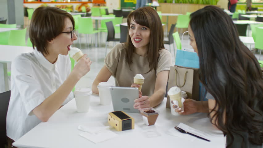 Tracking shot of three young female friends eating ice cream cones in cafe and discussing something they see on tablet computer screen #1011377129