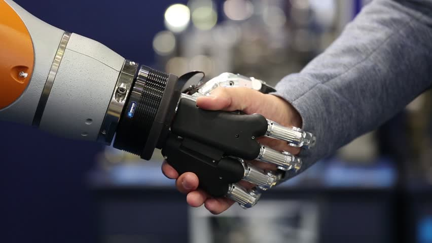 Moscow, Russia - May, 2018: Robot hand shaking human hand. Schunk gripper demonstration #1011393197