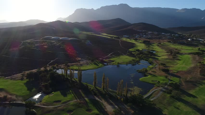 High aerial drone shot over a green golf course with lake in South Africa