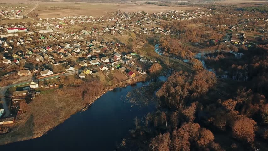 AERIAL: beautiful sunset over the European village in spring. Bird eye view on peaceful village in the middle of forest with ribbon-like river nearby