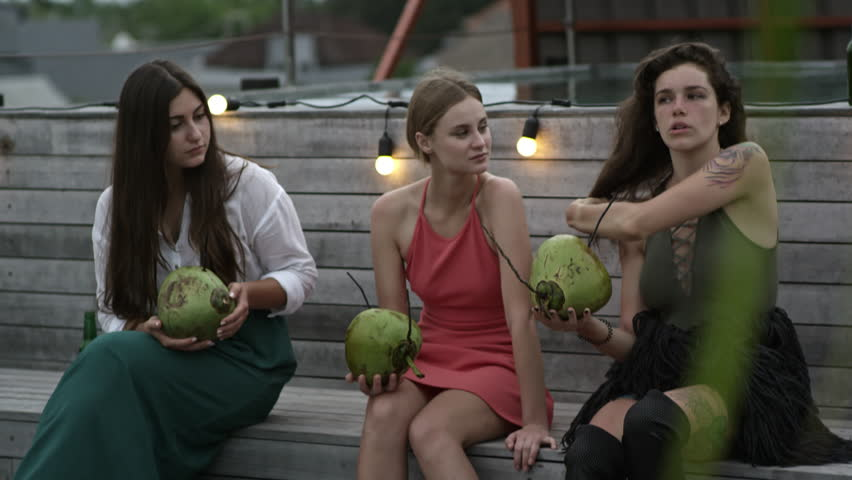 Three young women sitting on bench and talking to each other when drinking cocktails from young coconuts | Shutterstock HD Video #1011433046