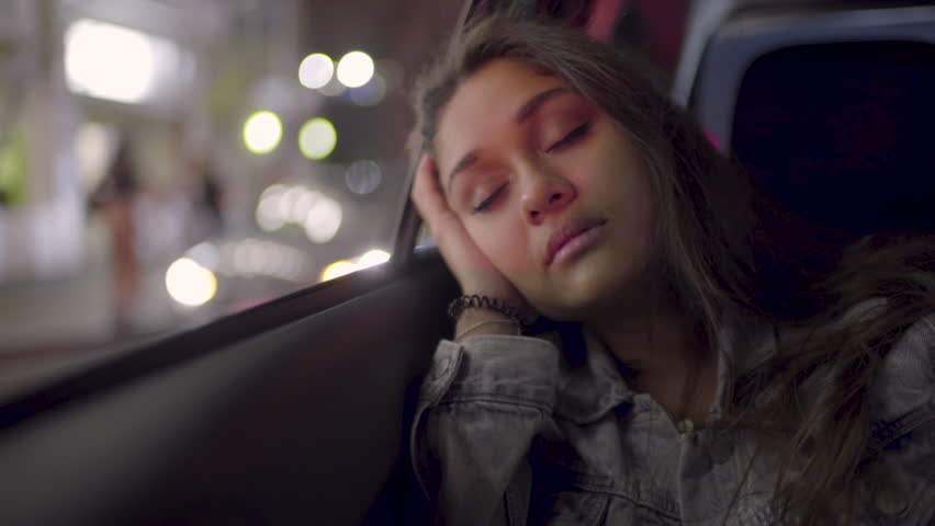 Portrait Of Young Woman Sleeping In Back Seat Of Moving Car, In City (Slow Motion)
