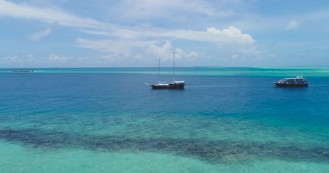 Beautiful Aerial shot around boat or Yacht at Ocean or sea with blue water and tropical Island in background