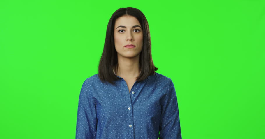 Young Caucasian offended beautifulwoman in the blue shirt standing in front of the camera on the chroma key background with crossesd hands. Green screen