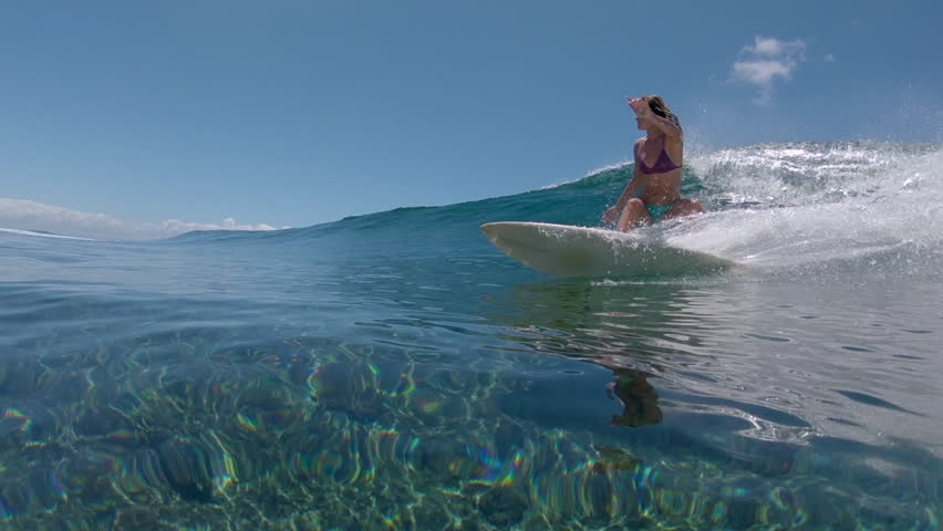 SLOW MOTION, LOW ANGLE, UNDERWATER: Joyful surfer girl carves a glimmering tube wave in spectacular Fiji. Cool young extreme surfboarder rides an amazing big barrel wave during her carefree holiday.   Shutterstock HD Video #1011449363