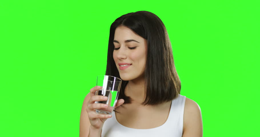 Close up of the beautiful young woman in the white T-shirt drinking water from the glass in front of the camera on the green background. Chroma key. | Shutterstock HD Video #1011449513