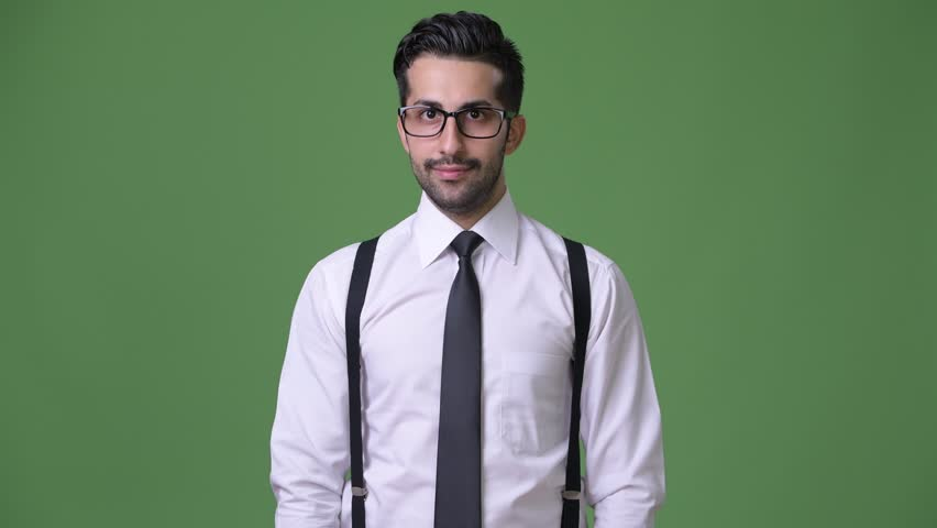 Young handsome bearded Persian businessman against green background | Shutterstock HD Video #1011456836