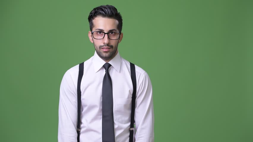 Young handsome bearded Persian businessman against green background | Shutterstock HD Video #1011456866