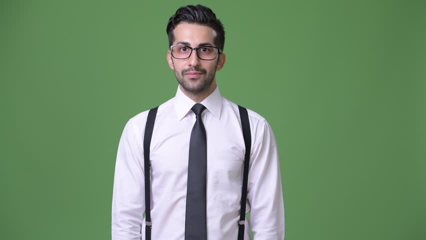 Young handsome bearded Persian businessman against green background | Shutterstock HD Video #1011456890