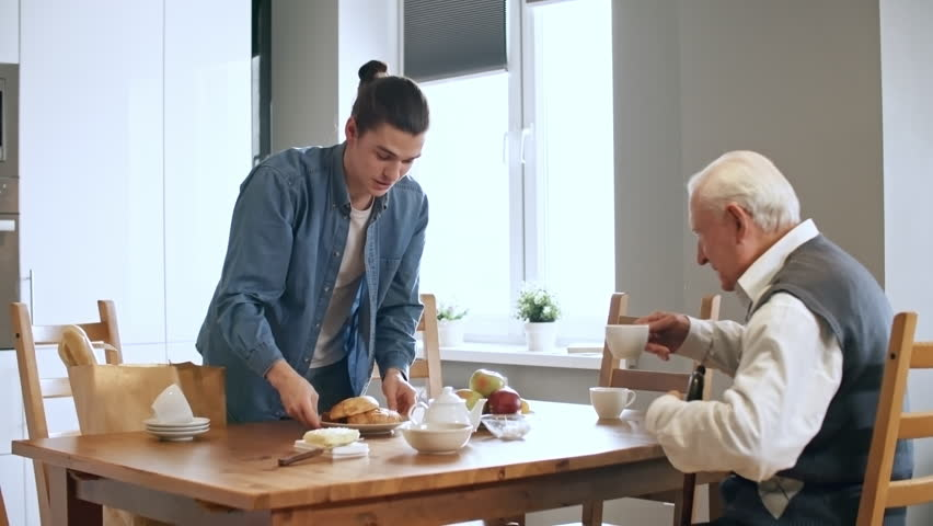 Medium shot of elderly man with walking stick sitting down at kitchen table and talking to young male caregiver pouring him tea and serving breakfast