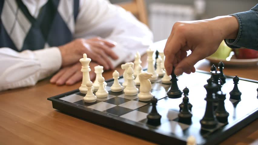 PAN with mid-section of hands of unrecognizable young and senior men playing chess