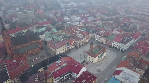 4k Aerial Drone Pan Arc of Tarnow, Poland's Main Square and Church During Foggy/Hazey Morning in Eastern Europe