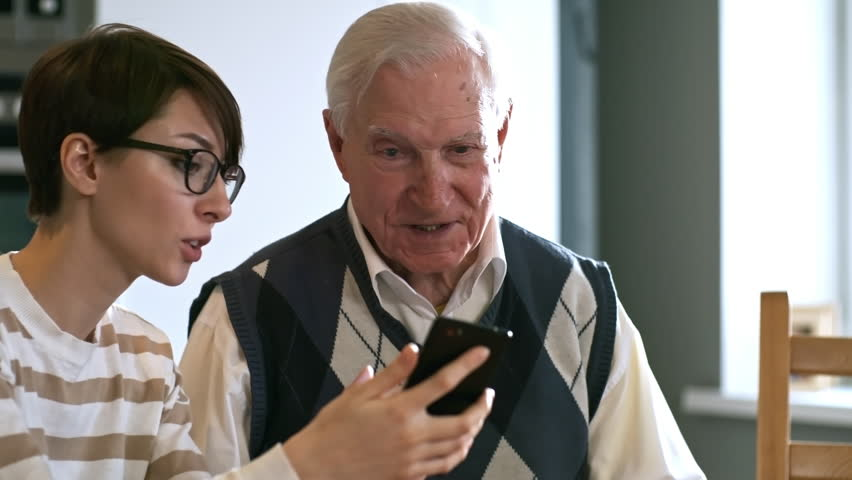 Tilt up of cheerful young woman in glasses showing mobile phone to senior man and teaching him how to use it