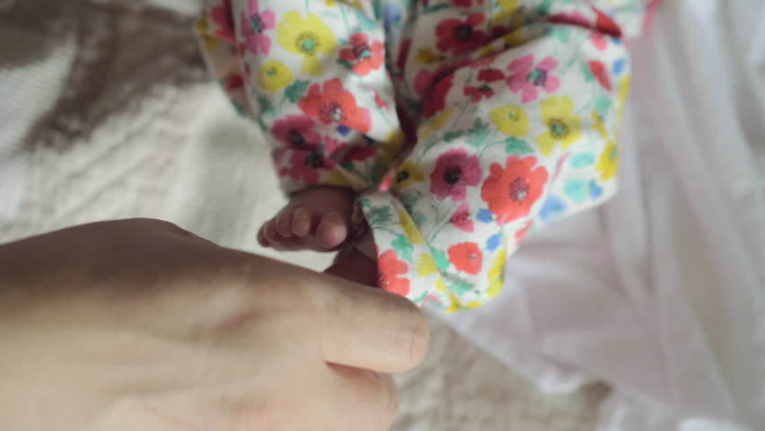 Slow motion close-up shot of grandpa hand touching carefully little feet of baby grandchild