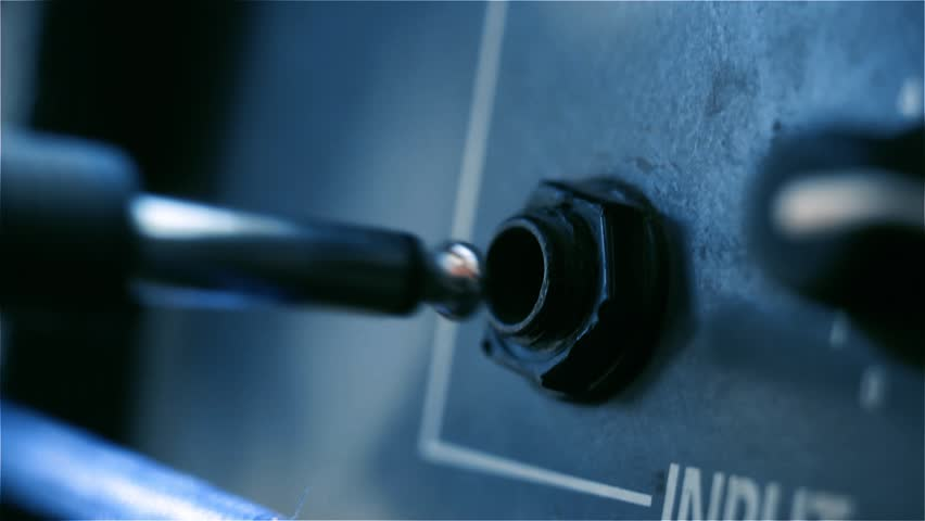 Male Hand plugging Jack Cable into Guitar Amplifier. Blue Tone. Close-Up.