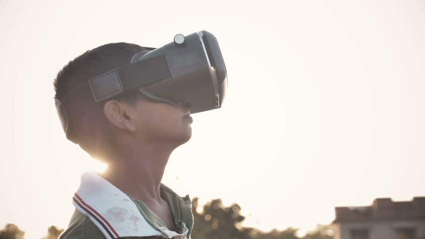 A young kid wearing VR glasses enjoying and looking around in amazement in an outdoor open field against the sun. An excited young boy wearing Virtual Reality glasses in rural India Royalty-Free Stock Footage #1011505298