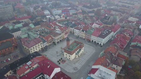 Foggy/Hazy Day in Tarnow Poland - 4k Drone Shot of Main Old Town Square and Colorful Red Roofed Buildings. Church sits in the Middle of Frame