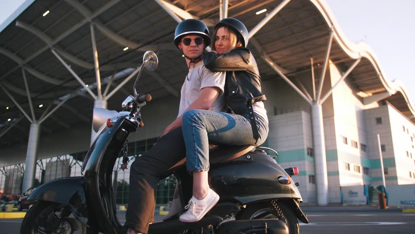 Happy young couple riding vintage scooter on urban background and having some fun, slow motion | Shutterstock HD Video #1011514250