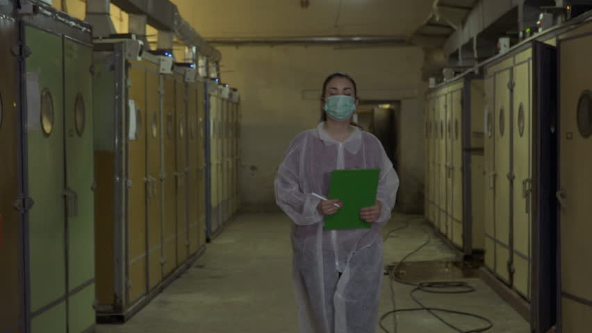 Inspector in protective overalls write report after checking incubators #1011522221