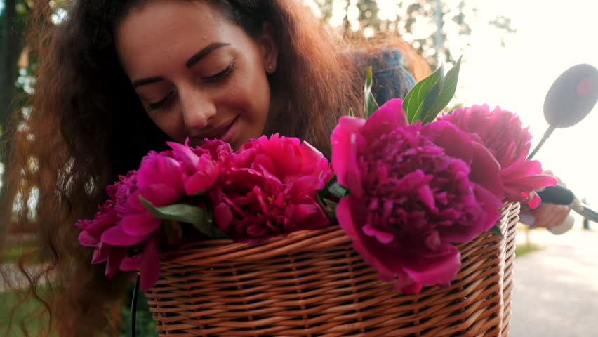Woman with curly hairstyle sniffs pink peony which are in wooden basket on her bike. Girl smells aromatic bouquet Slow motion. #1011525953