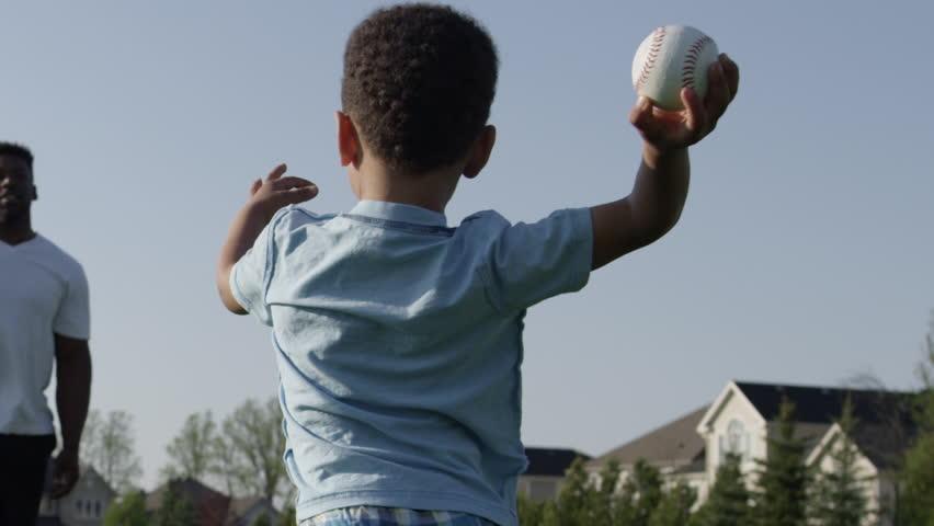 Little boy throwing baseball to dad