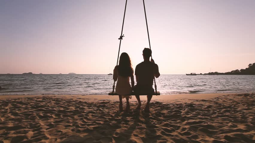Romantic getaway, couple in love sitting together on rope swing at sunset beach, silhouettes of young man and woman on holidays or honeymoon